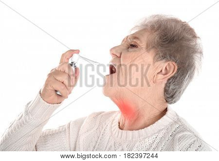 Allergies and sore throat concept. Sick senior woman using spray on white background