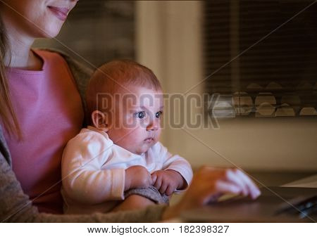 Unrecognizable young mother at home at night with her little baby son sitting on her lap, working on laptop