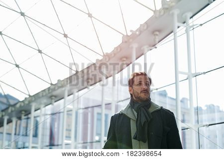 Young man at the station illuminated by the sunlight through the glass window