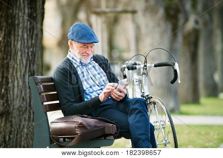 Handsome senior man with bicycle in town park sitting on bench, holding smart phone, texting. Sunny spring day.