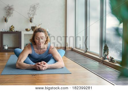 Portrait of peaceful girl developing her flexibility in yoga. She is sitting and bending her upper body to legs. Her eyes are closed with gentle smile