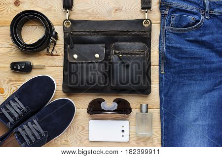 Young man accessories in casual style, fashion industry, bag, jeans, shoes, belt, eyeglasses, mobile phone, car key and perfume on brushed wood background
