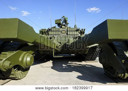 Demining military vehicle, armored mine clearing tank of green color, mine detector transportation, modern heavy army industry, blue sky on background
