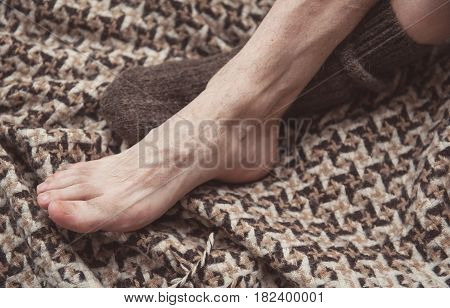 Man Feet On Woolen Plaid In Woolen Sock. Cozy Concept