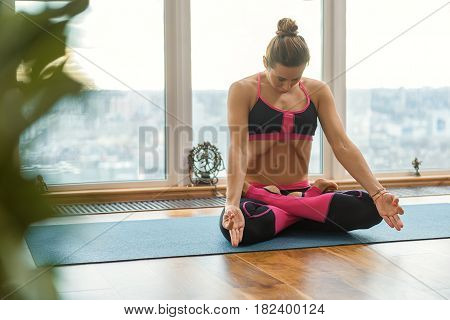 Fit young girl is doing breathing exercise. She is sitting on mat in lotus position near window. Her eye are closed with serenity