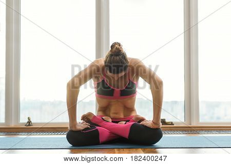 Peaceful female yogi is doing breathing exercise. Her abdomen is strained. Girl is sitting in lotus position on floor