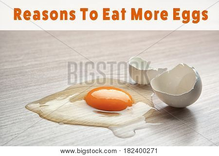 Raw broken egg on wooden background. Text REASONS TO EAT MORE EGGS