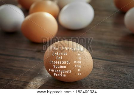Raw egg and list of nutrition facts on wooden background