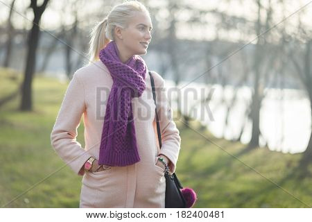 Beautiful woman in coat with scarf at spring park