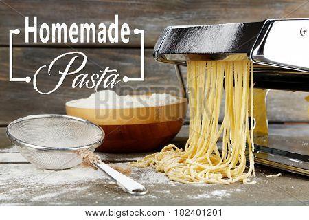 Raw homemade pasta, sieve and machine on wooden background
