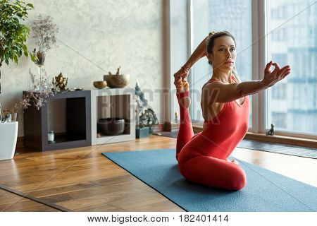 Portrait of confident young woman sitting in yoga position and stretching leg up to arm. She is looking forward with concentration
