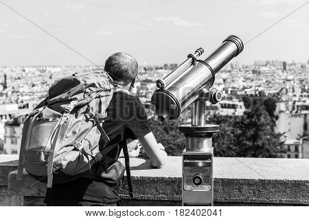 Paris France - July 06 2016: Rear view of man tourist with a backpack looking over Paris landscape from observation deck of the Montmartre with telescope. Montmartre area is popular among tourists in Paris. Black and white.