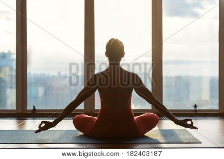 Peace and relaxation. Serene young girl is meditating in front of window. She is sitting on flooring and stretching arms sideways with fingers connected. Focus on her back