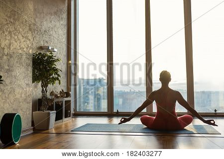 Fit young female yogi is enjoying meditation near window. She is sitting in lotus position and stretching hands sideways with relaxation. Focus on back