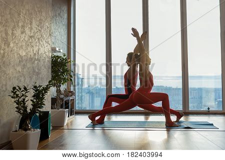 Sensual female yogis are creating beautiful shape by their body. They are standing in position and raising arms up with confidence