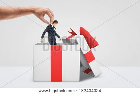 A large male hand getting a tiny businessman out from a white gift box with a red bow on white background. New employees. Management issues. Company transfer.