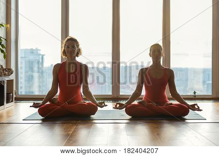 Happy young women are meditating with relaxation near window. They are sitting in lotus position and smiling