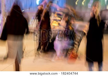 Abstract vintage tone motion, blurred image of street musicians and spectators in city, night urban street life, motion blur concept, for background use