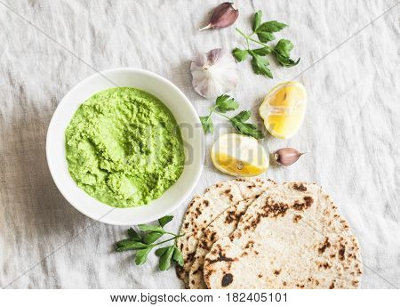 Green avocado dip and gluten free flatbread on a light background top view. Healthy vegetarian snack