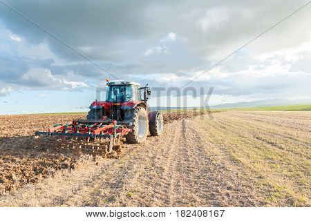 farmer with tractor ploughing the land at sunset
