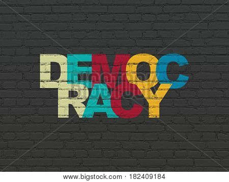 Political concept: Painted multicolor text Democracy on Black Brick wall background