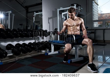 Young man is training biceps while sitting with dumbbells in the gym