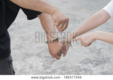 A man and woman's hands are handcuffed together. no freedom