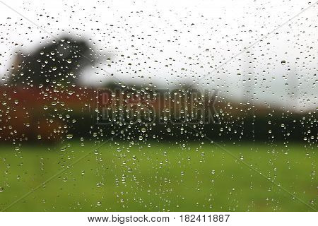 Raindrops on a window pane blurred landscape in background