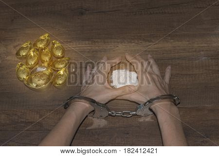 The chrome metal handcuffed bondage on man hand during holding gold bar represent the crime fraud and punishment equipment concept related idea. Addictive substance no freedom Translation in English meaning lucky and richly