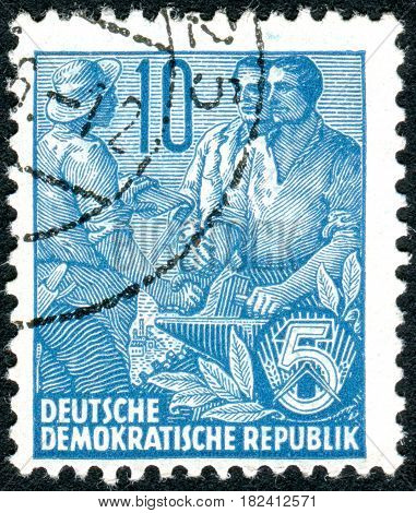 GERMANY - CIRCA 1955: A stamp printed in Germany (GDR) is dedicated to the five-year plan shows worker peasant and intellectual circa 1955