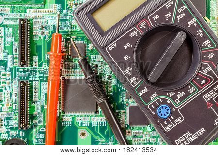 Digital multimeter and probes on a green circuit board closeup