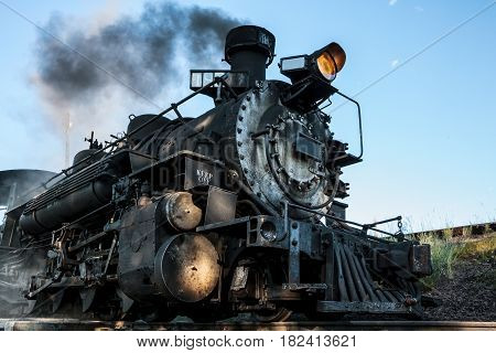 A vintage steam locomotive is fully stoked and ready to go.