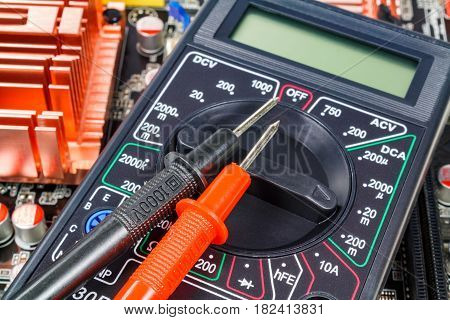 Digital multimeter with probes on the computer motherboard closeup