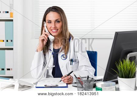 Smiling Female Doctor Sat At Desk With Telephone To Ear