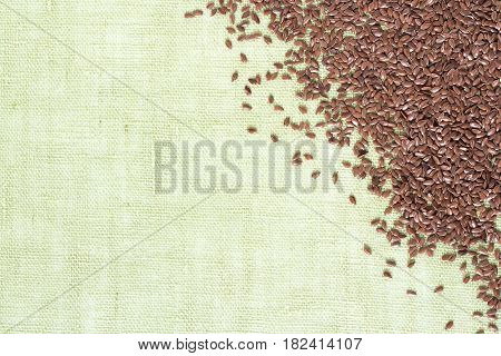 background of dry flax seeds on linen napkin.