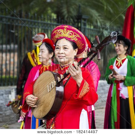 Hanoi, Vietnam - Jan 27, 2016: Vietnamese woman in traditional dress and hat playing Tranh instrument on Tet holiday at Van Mieu (Temple of Literature), Hanoi capital.