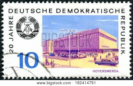GERMANY - CIRCA 1969: A stamp printed in Germany (GDR) dedicated to the 20th anniversary of the GDR shows the Arms of Republic and View of Hoyerswerda circa 1969