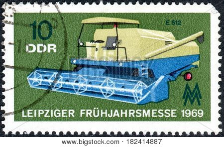 GERMANY - CIRCA 1969: A stamp printed in Germany (GDR) dedicated to Leipzig Spring Fair shows the Combine harvester circa 1969
