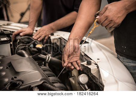 Close up man hands. Mechanic checking level of new engine oil .