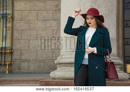 Portrait of young beautiful fashionable woman posing on street. Lady wearing stylish red hat and handbag, emerald topcoat. Female fashion concept. City lifestyle