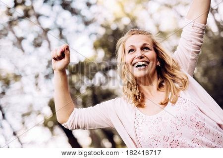 Beautiful young woman being happy outdoors and raising hands