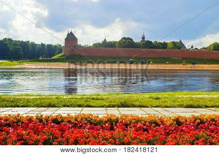 Architecture landscape of Novgorod Kremlin and water area of Volkhov river with flowerbed on the foreground in summer cloudy day Veliky Novgorod Russia. Architecture view of Veliky Novgorod Russia