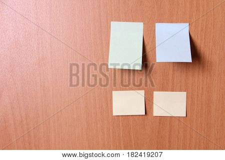 Empty sheets of paper on a wooden wall