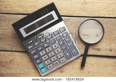 The calculator and magnifying glass - objects for economic calculations