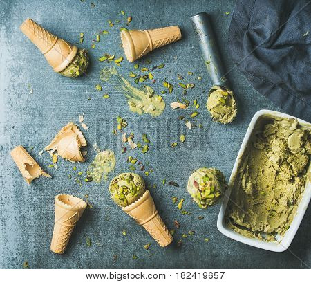 Homemade pistachio ice cream in ceramic mold and metal scooper with crashed pistachio nuts and waffle cones over grey concrete background, top view, copy space