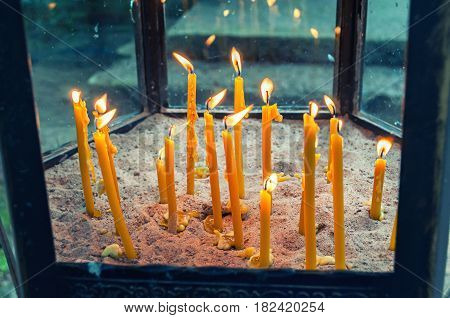 Church candlestick with burning church candles inside standing on the sand. Burning candles near the church. Church objects -closeup view. Church candlestick with burning church candles