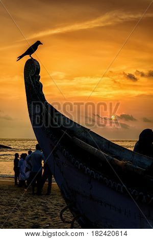 Bird perched on boat rostrum at sunset with sea in background
