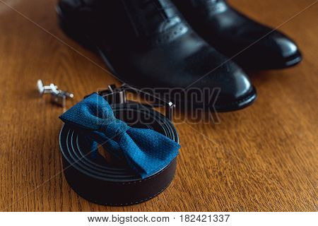Close up of modern man accessories. Blue bowtie, leather shoes, belt and cufflinks.