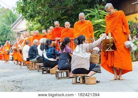 Luang Prabang, Laos - Mar 06 2015: Buddhist Monks Collecting Alms In The Morning. The Tradition Of G