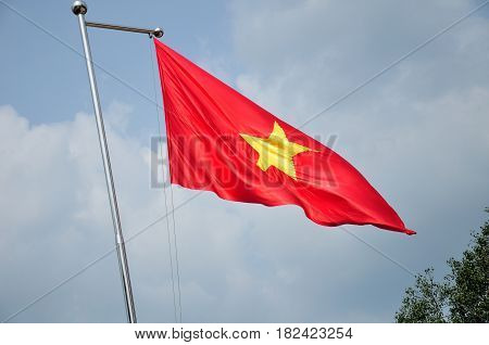 The vietnamese flag flying from a flag pole against the sky in the ben Douc scenic area in south vietnam.
